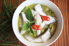 Green curry coconut soup Thai style with fish meat. Close up top view of green curry coconut soup Thai style with fish meat in white bowl on bamboo plate mat Stock Photos
