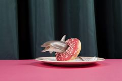 Green curtain and dolphin donut buoy. A dolphin plastic toy inside a donut symbolizing a buoy on a vibrant green curtain and pink background. Minimal funny and royalty free stock photos
