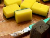 Green cutter cutting Dishwashing sponge into sections. Yellow Dishwashing sponge on Tiled floor royalty free stock photos