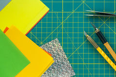 Green cutting mat with art knives, tweezers and paper crafts. Stock Photography