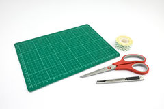 Green cutting mat with cutter  Scissors and Tape roll of double- Royalty Free Stock Photography