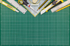 Green cutting mat on desk with school or office supplies Stock Image