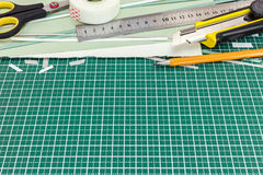 Green cutting mat with various school tools and office supplies Royalty Free Stock Images