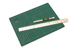 Green cutting mats with iron ruler and cuter Royalty Free Stock Images