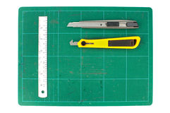 Green cutting mats with iron ruler and cuter on white background.  Royalty Free Stock Image