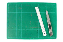 Green cutting mats with iron ruler and cuter on white background.  Stock Photo