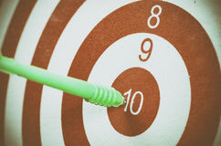 Green dart arrow hitting in the target center of dartboard Stock Image