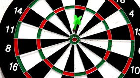 Green dart hitting the bullseye on white background stock footage