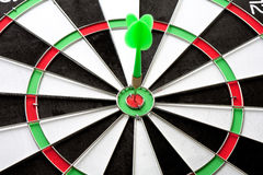 Green dart punctured in the center. Of the target stock photo