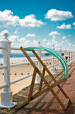 Green Deckchair. Deckchair blowing in the wind at an English seaside Stock Photos