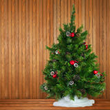 Green Decorated Christmas Tree on Wooden Background. Royalty Free Stock Images