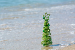 Green decorative Christmas tree shining in the sand Royalty Free Stock Photography