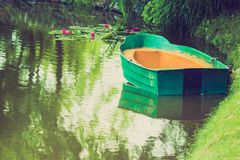 Green decorative wooden boat on lake water. Green decorative wooden boat on calm lake water. Idyllic garden decorations concept Stock Photo