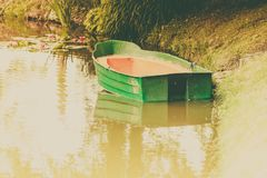 Green decorative wooden boat on lake water. Green decorative wooden boat on calm lake water. Idyllic garden decorations concept Stock Photos
