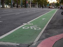 Green dedicated bike lane along city street in evening. Green dedicated bike lane along city street in the evening stock images