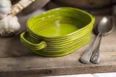 Green Deep Dish, Spoons, and Garlic on Wooden Counter Stock Photography