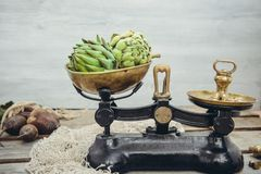 Green delicious artichoke vegetables on the vintage weights, standing on the rustic wooden background. Farmer local market counter. Kitchen table. Copy space royalty free stock photo