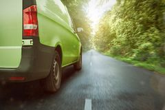 Green delivery van driving through the forest royalty free stock photos