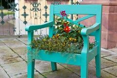Green den gammala stolen som dekoreras med färgrika blommor Fotografering för Bildbyråer