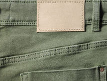 Green denim textile for background back closeup with leather label Stock Photography