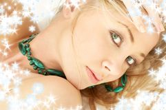 Green desire with snowflakes. Portrait of laying green-eyed blond girl with snowflakes Stock Photography