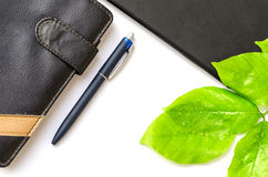 Green desktop diary pen tablet foliage background Stock Photography