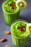 Green detox smoothie close up. Green smoothie with kiwi, apple, spinach, banana and almond milk close up decorated with pomegranate grains stock images