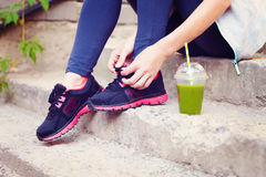 Green detox smoothie cup and woman lacing running shoes before w Royalty Free Stock Images