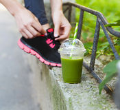Green detox smoothie cup and woman lacing running shoes before w Stock Photo