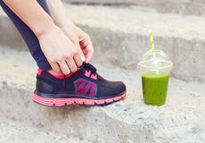 Green detox smoothie cup and woman lacing running shoes before w Stock Images