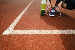 Green detox smoothie cup and woman lacing running shoes before w. Orkout. Fitness and healthy lifestyle concept Stock Photo