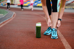 Green detox smoothie cup and woman lacing running shoes before w. Orkout. Fitness and healthy lifestyle concept Royalty Free Stock Photography