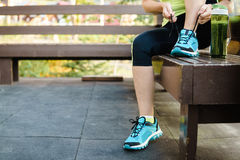 Green detox smoothie cup and woman lacing running shoes before w. Orkout. Fitness and healthy lifestyle concept Royalty Free Stock Photo