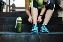 Green detox smoothie cup and woman lacing running shoes before w. Orkout. Fitness and healthy lifestyle concept Stock Images
