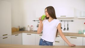 Green detox smoothie - healthy woman drinking vegetable smoothie. Happy young woman drinking fresh green juice enjoying