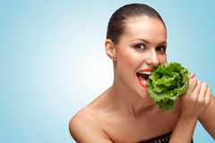 Green diet. A creative portrait of a beautiful hungry girl on a diet eating green leaves of lettuce Royalty Free Stock Photography