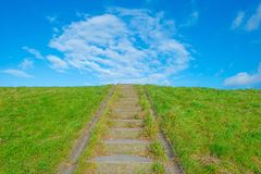 Green dike with a stairway below a blue cloudy sky. In sunlight Royalty Free Stock Image