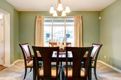 Green dining room interior with classic brown furniture. Royalty Free Stock Image