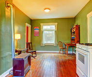 Green dining room near kitchen with stove. Stock Photos