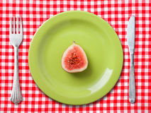 Green dinner plate with fig. Green dinner plate with fork and knife on red and white checked tablecloth, with a fig Stock Photography