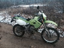 Green dirt bike in mud and snow covered trails. Stock Images
