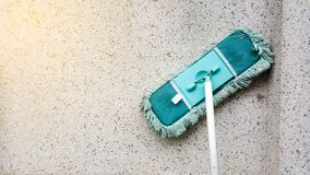 A green dirty mob or swab lean on dirty concrete wall. The floor mop is used to clean the floor clean. Cleaning and exercise by ho. Usework concept stock photography