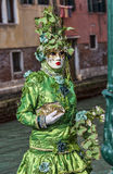 Green Disguise. Venice, Italy- February 18th, 2012:Environmental portrait of a person in sophisticated green Venetian costume posing in Sestiere Castello during royalty free stock photo