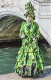Green Disguise. Venice, Italy- February 18th, 2012:Image of a person in sophisticated green Venetian costume posing in Sestiere Castello during The Venice stock photo