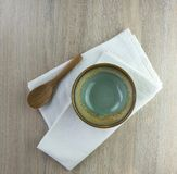 Green dishe and wood spoon. On a wooden table Royalty Free Stock Photos