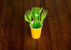 Green disposable forks in yellow plastic cup, on wooden surface. Green disposable forks in yellow plastic cup, on dark wooden surface Royalty Free Stock Photos