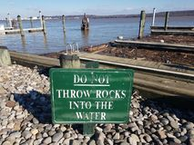 Green do not throw rocks into the water sign with docks and debris. And stones stock photography