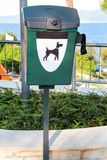 Green dog waste container in a tourist complex near the sea / Public trash can for dog waste poop sign. Green dog waste container in a tourist complex near the Royalty Free Stock Image