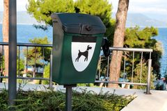 Green dog waste container in a tourist complex near the sea / Public trash can for dog waste poop sign. Green dog waste container in a tourist complex near the Royalty Free Stock Photography