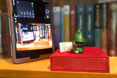 A green doll reading book & seeing Tablet with soft focus of book shelf Royalty Free Stock Photography